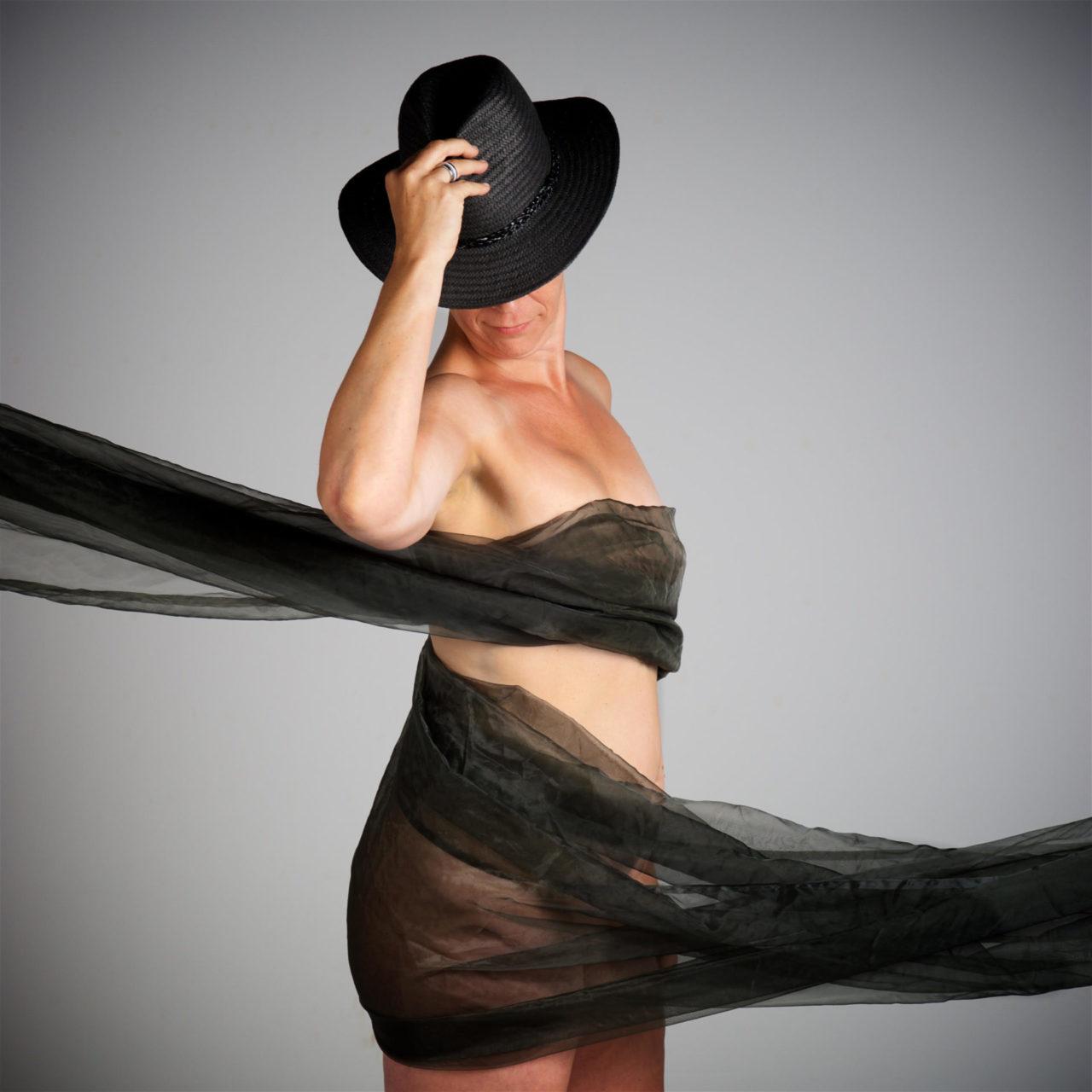 De vrouw draagt enkel een tule doek, hoed en ring